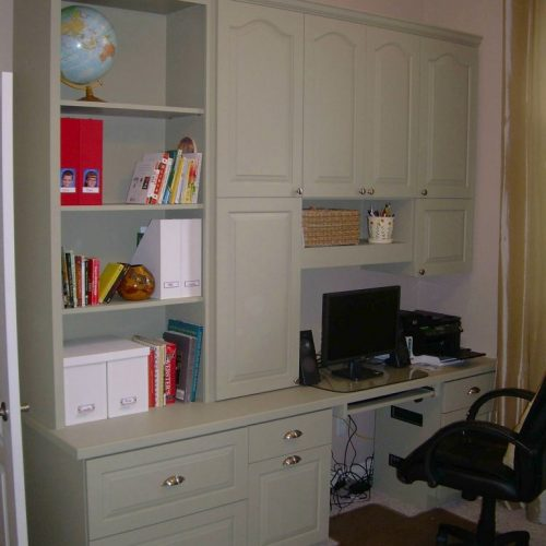 A built-in desk with bookcase and cabinets